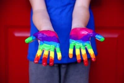 Due mani verniciate con colori dell'arcobaleno